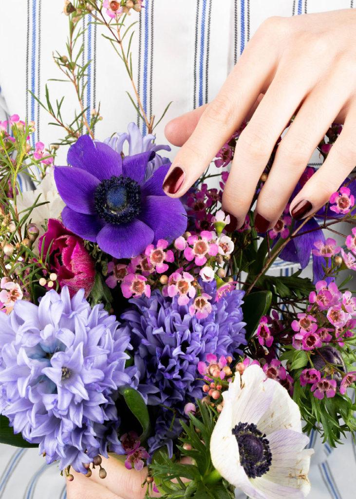 mains manucurée nailmatic qui tiennent un bouquet