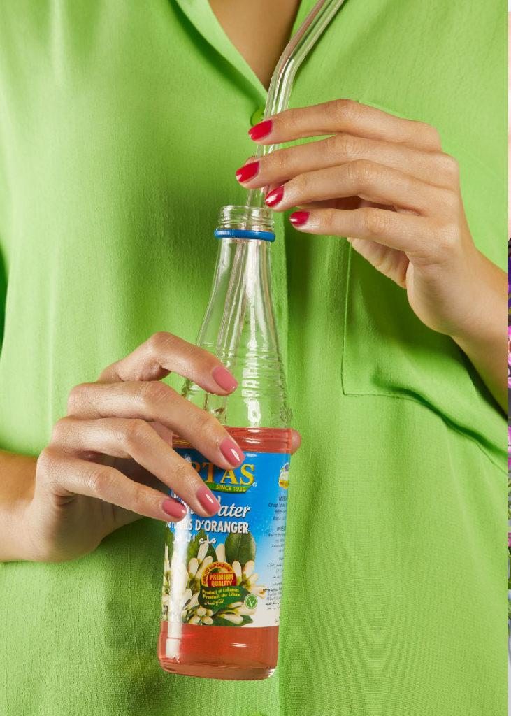 mannequin avec une manucure nailmatic. Tiens une bouteille en verre entre les mains